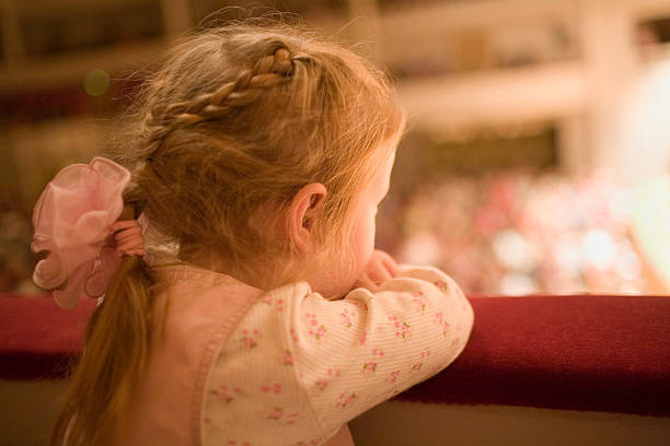 Little girl at the theater stock photo