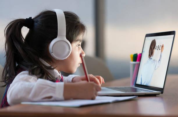 Little girl attending to online school class
