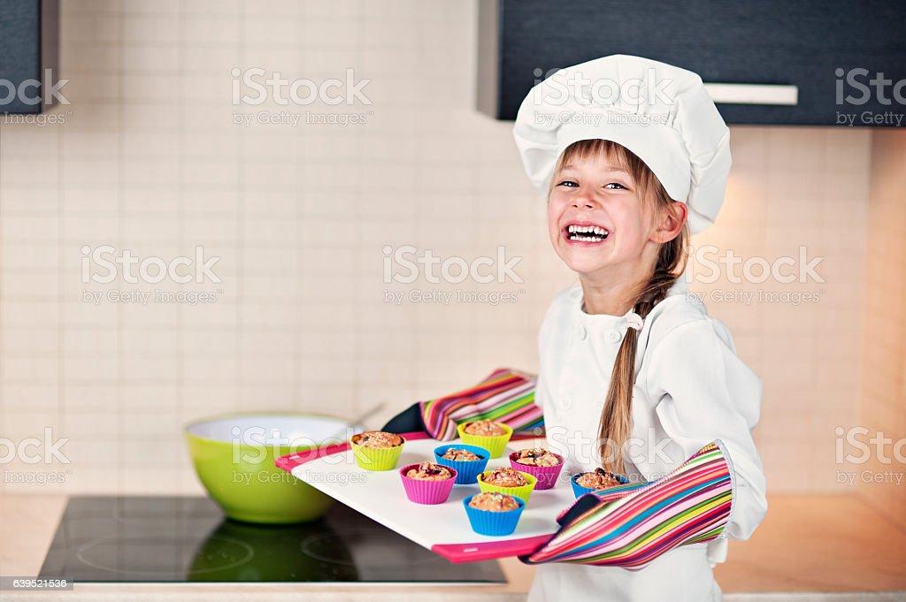 Little girl baking cupcakes stock photo