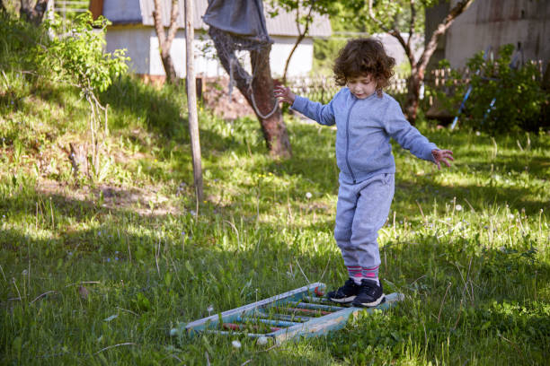 Little girl balancing herself while walks on the wooden ladder lying on the grass stock photo