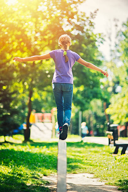 little girl balancing on a balance beam in sunny park - balance beam stock photos and pictures