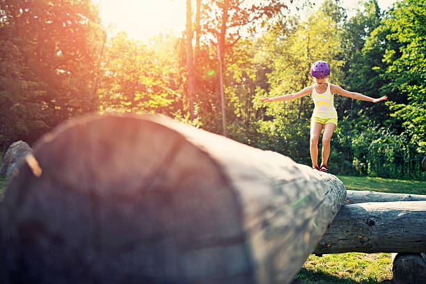 little girl balancing on a trunk in adventure park - balance beam stock photos and pictures