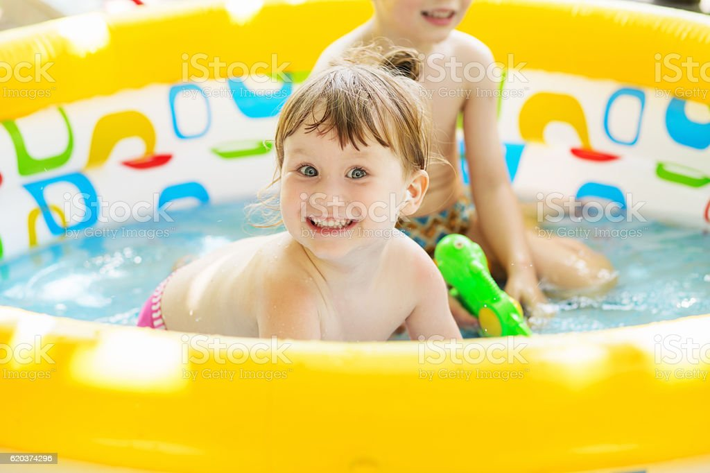 Little girl bathes in yellow Inflatable Swimming Paddling Pool o foto de stock royalty-free
