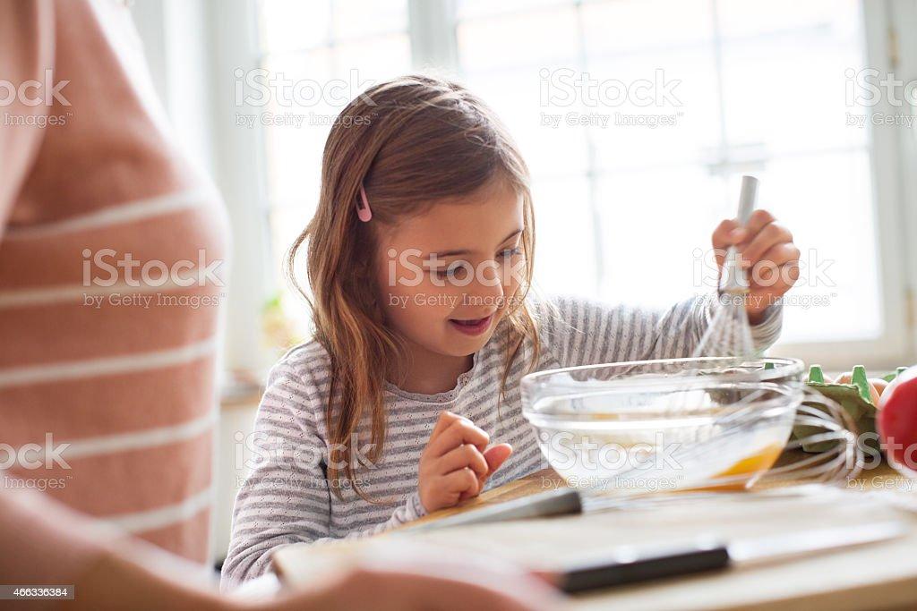 Little girl beating eggs in kitchen stock photo