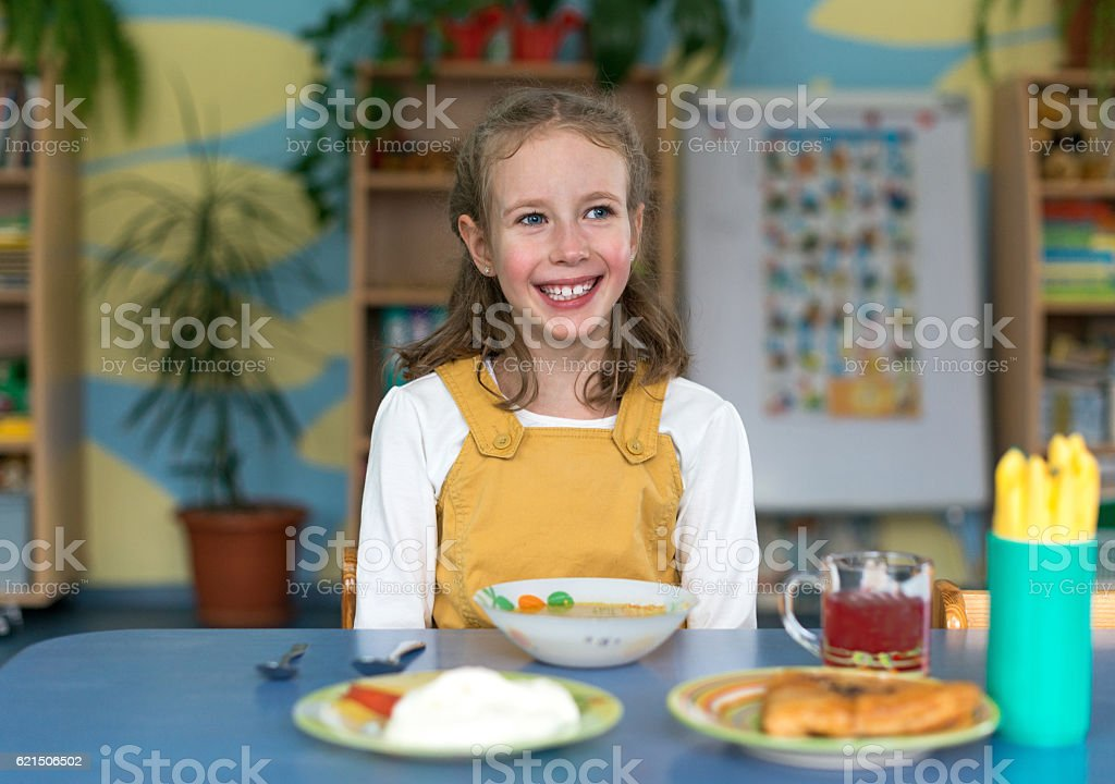 Little girl before lunch in kindergarten. photo libre de droits