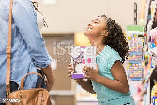 Young girl begs and pleads for her mom to buy her a toy while shopping.