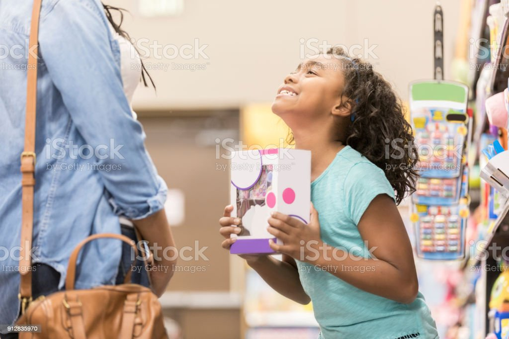 Little girl begs her mom to buy a toy stock photo