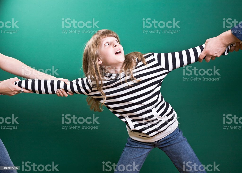 Little girl being pulled different directions stock photo