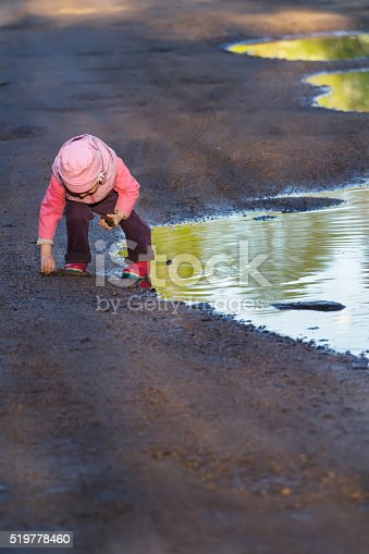 Little girl is bending to the ground playing in big spring puddle wearing purple nylon and pink bucket hat