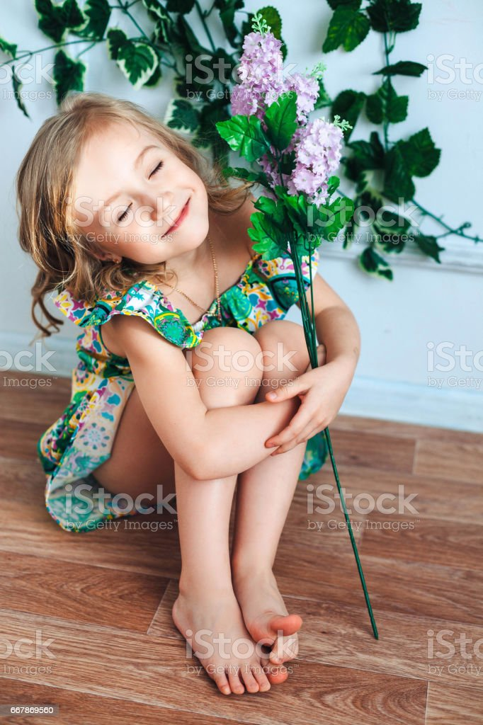Little girl blonde sits on the floor with a flower in her hand in a room, closed eyes and smiles stock photo