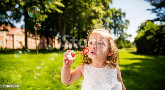 185267233 istock photo Little Girl blowing bubbles in park on a sunny day 174603220