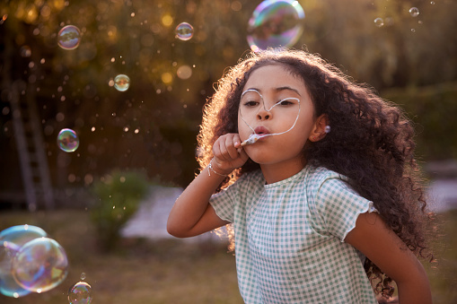 African-american cute little girl with curly hair blowing soap bubbles with heart-shaped hand-made wand in the garden during summer