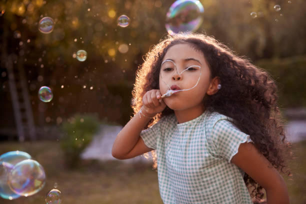 Little girl blowing bubbles with hand-made wand in the garden stock photo