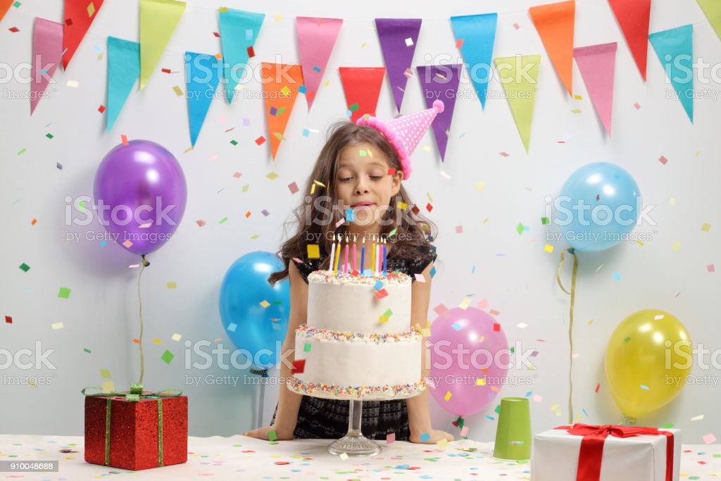 Little girl blowing candles on a birthday cake stock photo