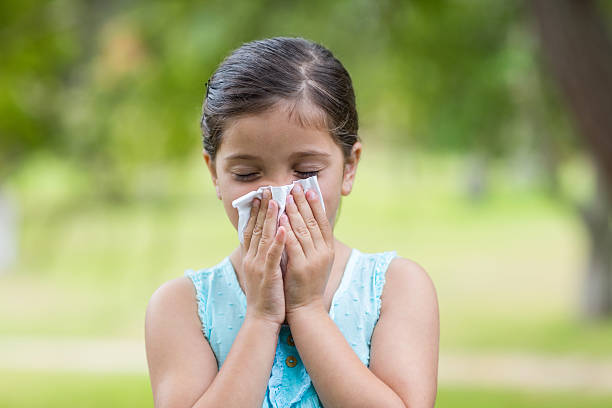 Little girl blowing his nose Little girl blowing his nose on a sunny day human parainfluenza virus stock pictures, royalty-free photos & images