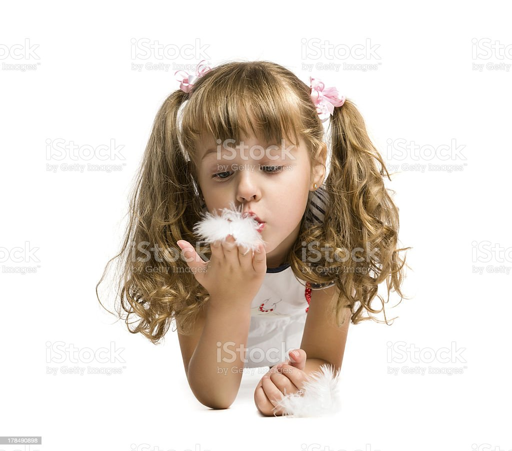 little girl blowing on a feather royalty-free stock photo