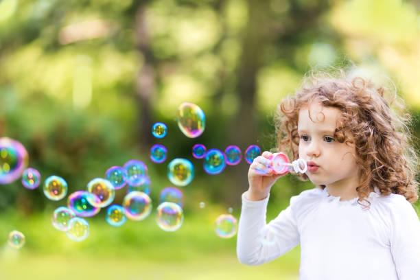 Kleines Mädchen bläst Seifenblasen im Sommerpark. – Foto