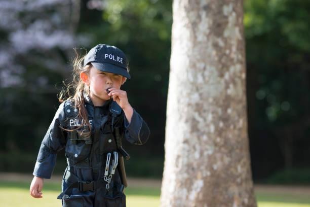 kleines mädchen bläst pfeift polizei kostüme tragen - coole halloween kostüme stock-fotos und bilder