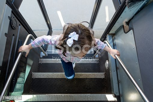 High angle view of a young schoolgirl boarding a school bus.