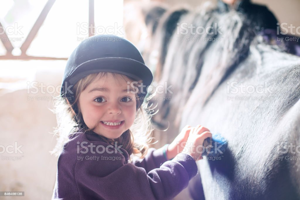 Petite fille se brosser son poney - Photo