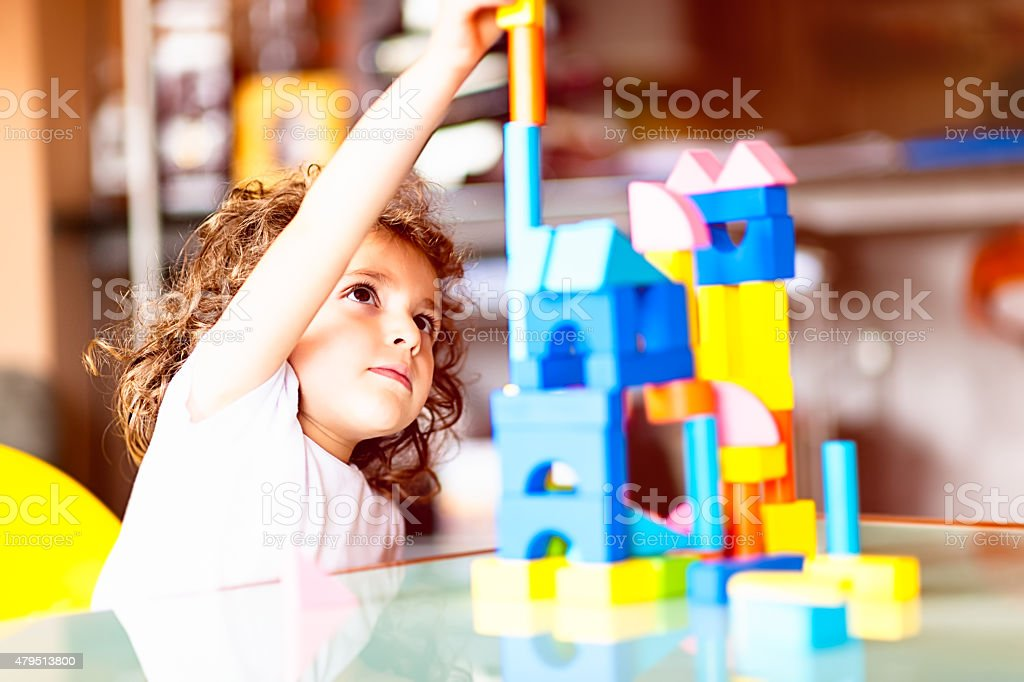 Little girl building a house with cubes stock photo
