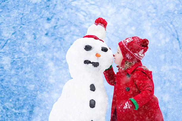 kleines mädchen gebäude ein schnee mann im winter - schneemann bauen stock-fotos und bilder