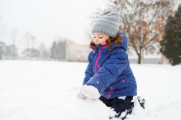 little girl building a snowman in winter nature - schneemann bauen stock-fotos und bilder