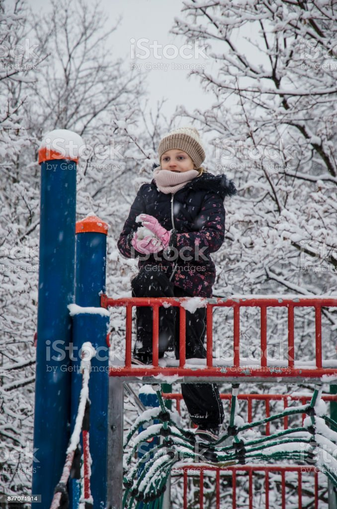 little girl building a snowman in winter park full of snow stock photo