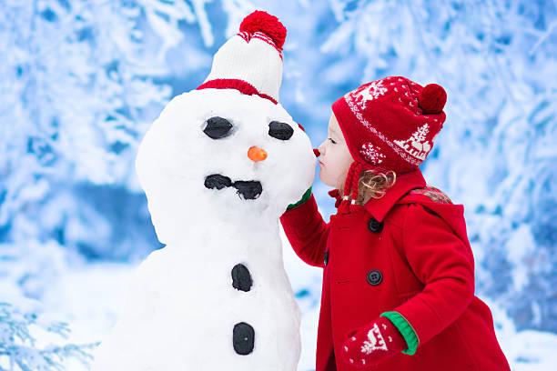 kleines mädchen gebäude schnee mann im winter - schneemann bauen stock-fotos und bilder