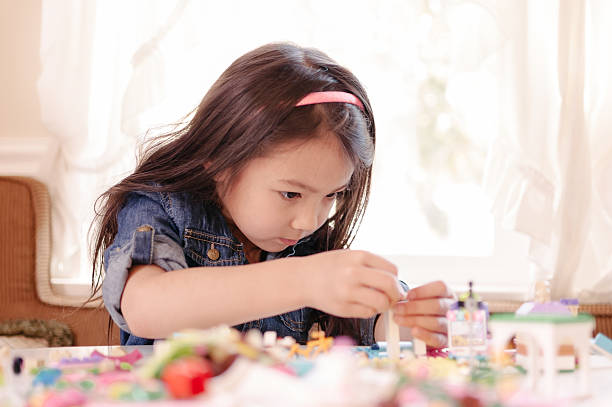 Little girl building something with her LEGO stock photo