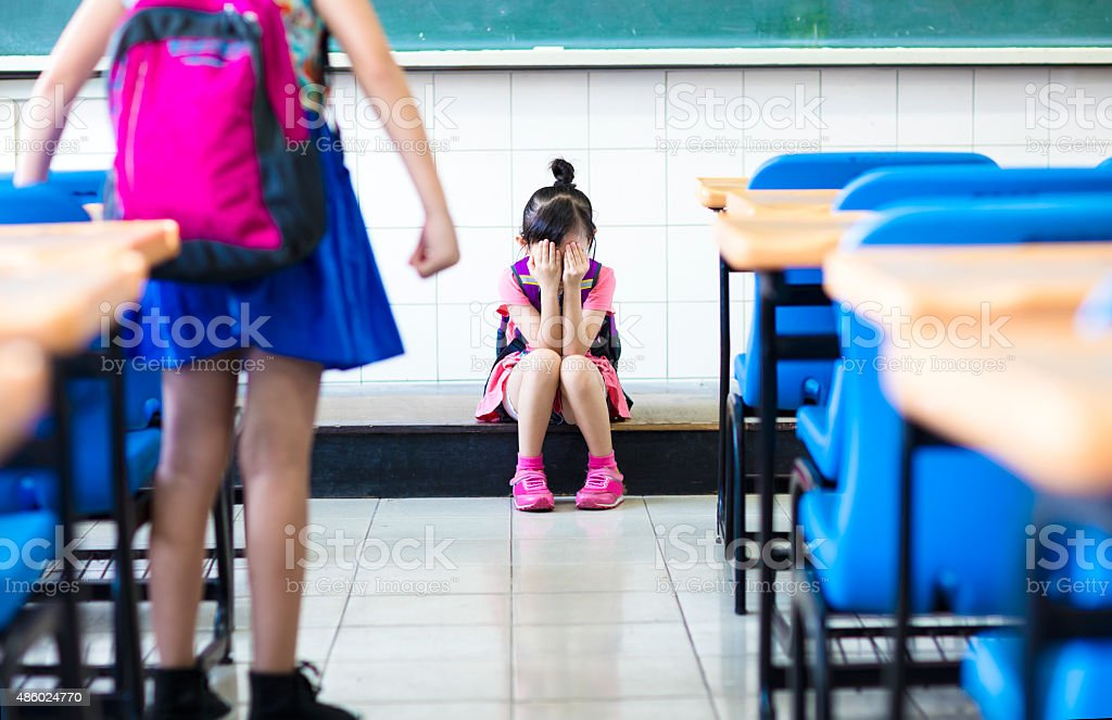little girl bullying in school classroom stock photo