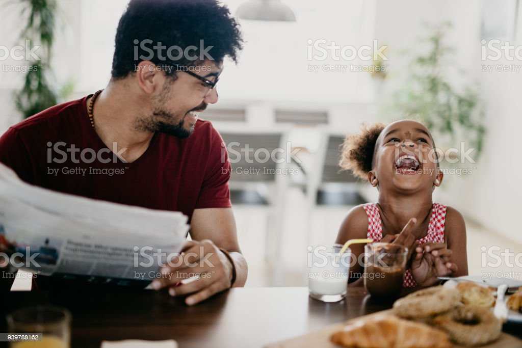 Little girl bursts into laugh while having breakfast with her father stock photo