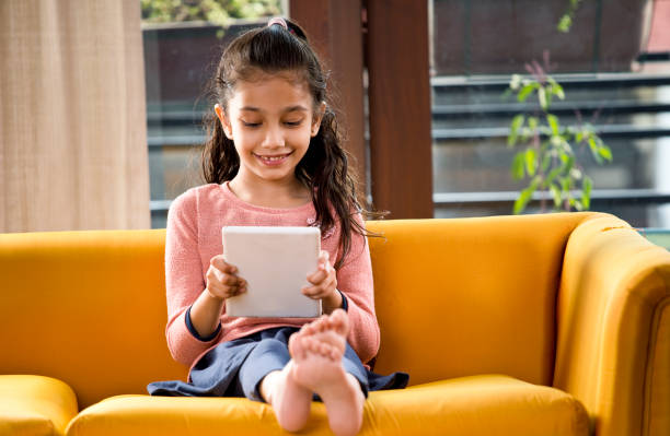 Little Girl busy on digital tablet at home stock photo