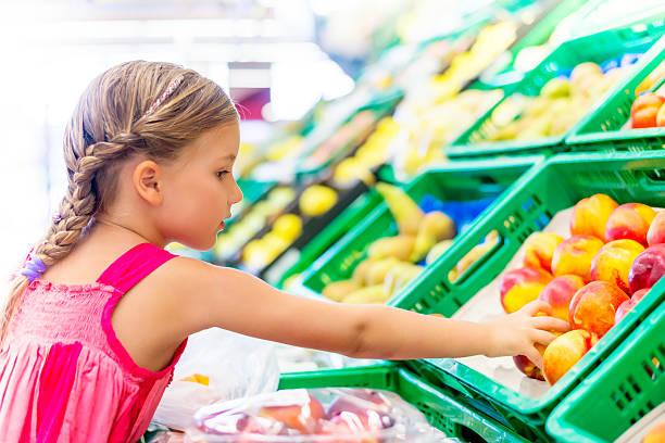 little girl buying healthy foods stock photo