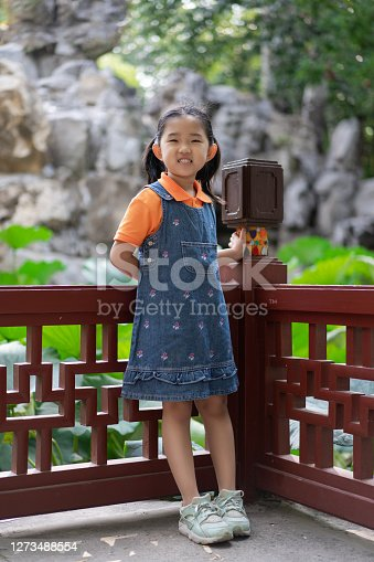 Little Girl by the Chinese Classical Style Garden Pond