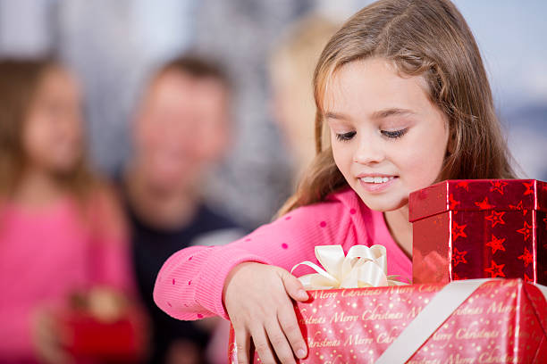 little girl carries stack of christmas presents. family background. - little girls giving head stock photos and pictures