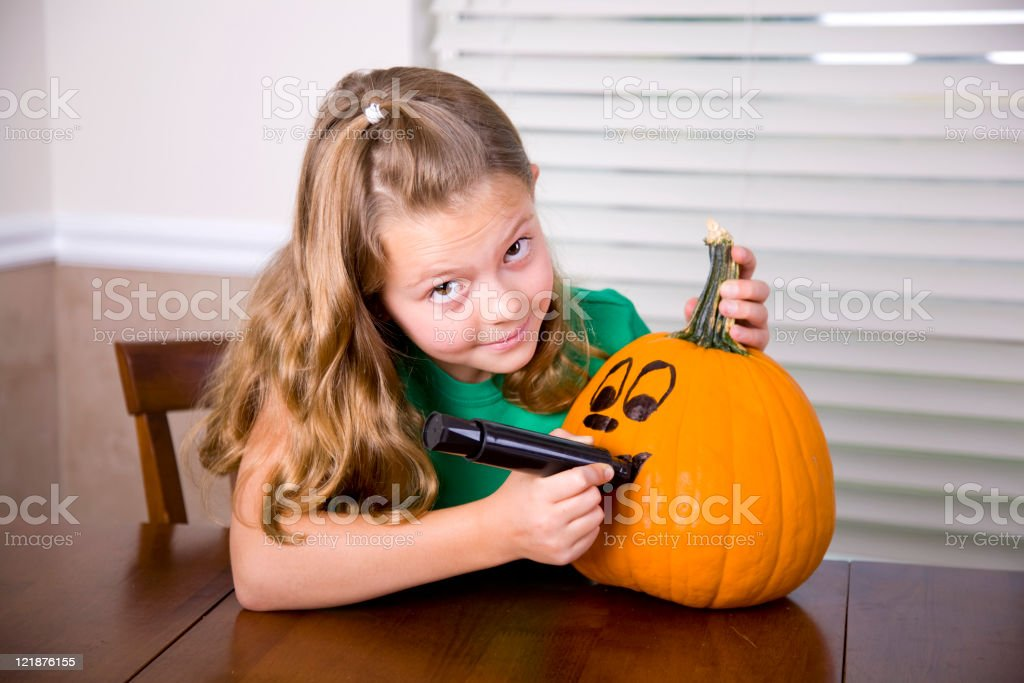 Little Girl Carving a Pumpkin royalty-free stock photo