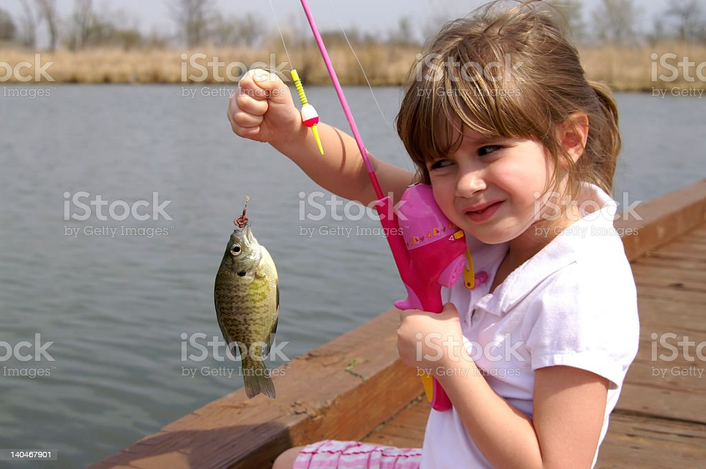 A little girl caught a fish on a wooden boat stock photo