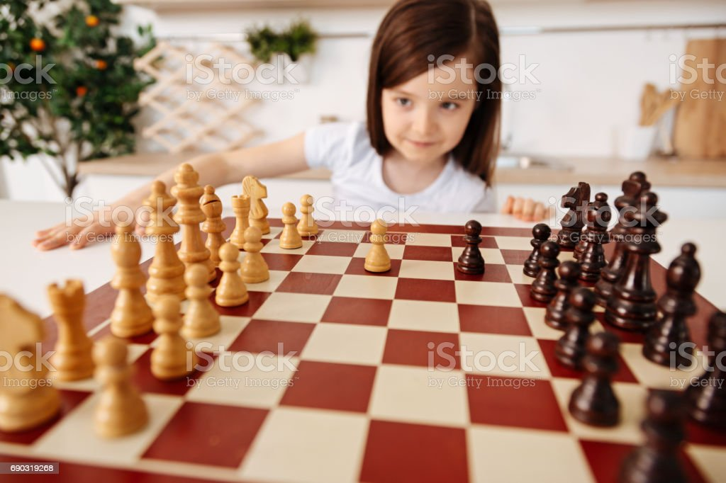 Little girl changing a perspective on a chessboard stock photo