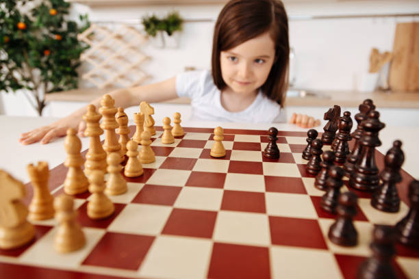 Little girl changing a perspective on a chessboard New vision. The focus being on the chessboard with two pawns in the middle while the background having a creative smart girl looking at the chessboard under a different angle child prodigy stock pictures, royalty-free photos & images