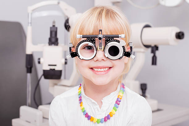 little girl checking her vision - optometrist stock pictures, royalty-free photos & images