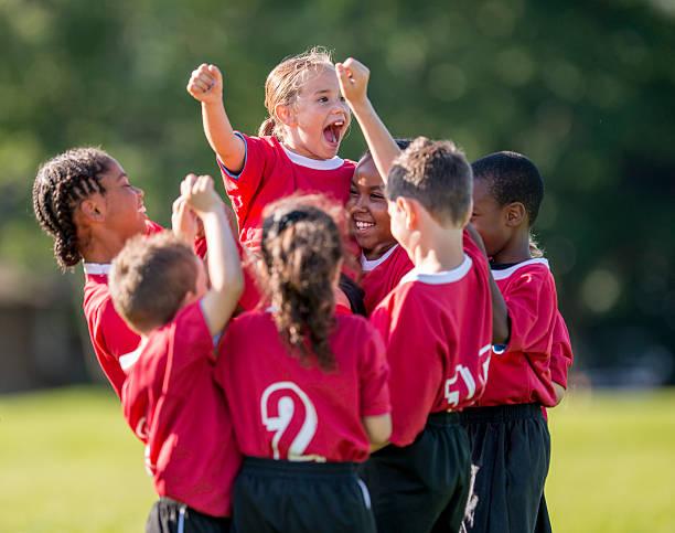 kleines mädchen jubeln im team-sitzung - fußball team stock-fotos und bilder