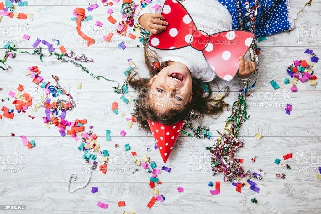 Pequeña niña linda y hermosa con confeti multicolor en el piso y un arco feliz feliz sombrero festivo - foto de stock