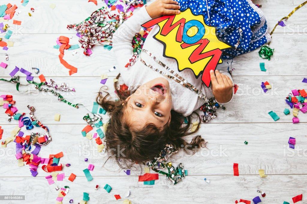 Pequeña niña linda y hermosa con confeti multicolor en el suelo feliz feliz con un wow de signo - foto de stock