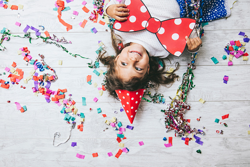 istock Little girl child cute and beautiful with multi-colored confetti on the floor and a festive hat happy happy bow 861947094