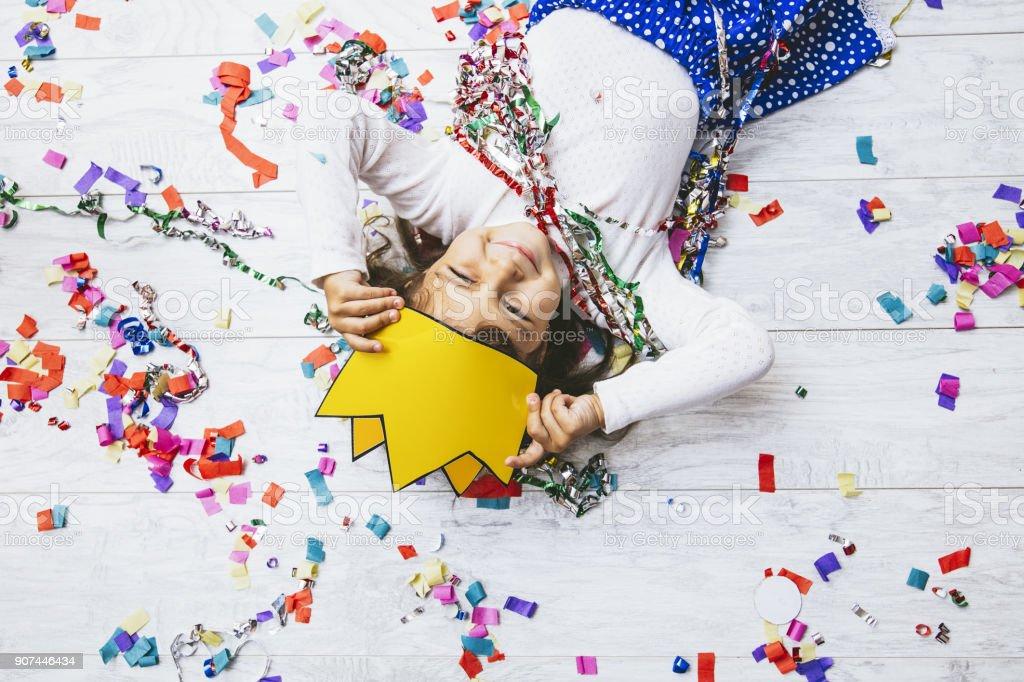 Pequeña niña linda y hermosa con confeti multicolor en el suelo feliz es feliz en una princesa de corona de papel - foto de stock