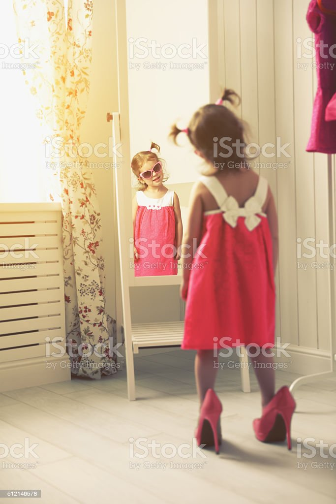 little girl child fashionista looking in the mirror at home stock photo