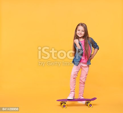istock little girl child in colorful clothes showing success gesture 641439956