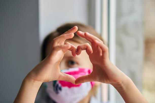Kleines Mädchen, Kind in Maske machen Herzen aus den Händen, Coronavirus Quarantäne – Foto