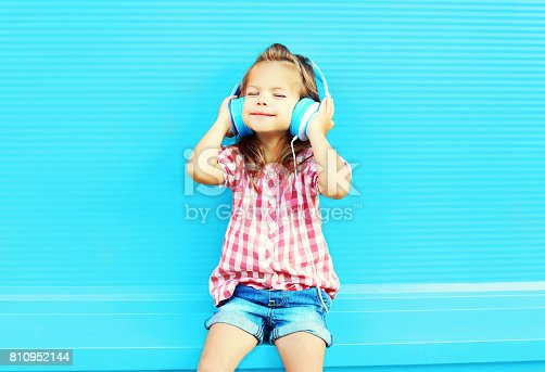 istock little girl child listens to music in headphones on a colorful blue background 810952144